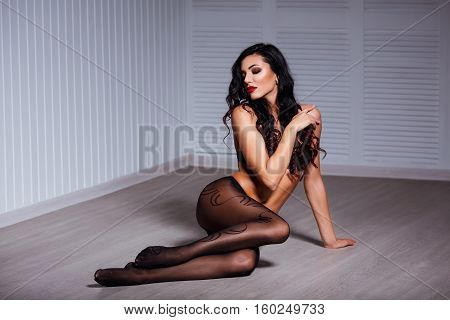 Perfect, sexy body, legs and ass of young woman wearing seductive lingerie amd tights shows her erotical torso, posing in a sensual way.