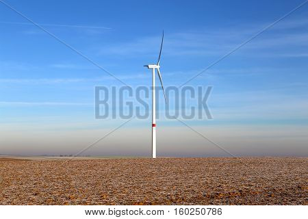 Windmill generator in wide yard / Yard of windmill power generatorunder blue sky, shown as energy industry concept