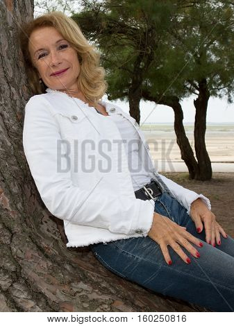 A Retired Woman Next To A Tree At The Water's Edge