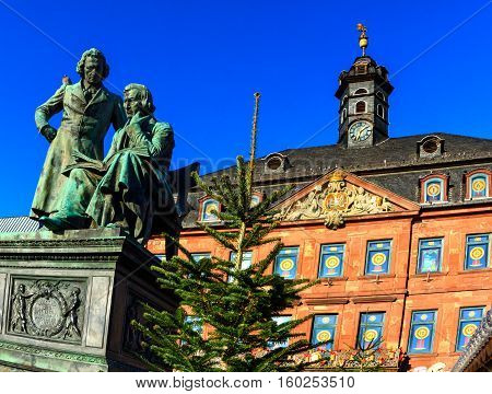 Brothers Grimm in front of the town hall in Hanau looking down at the Christmas market, Germany