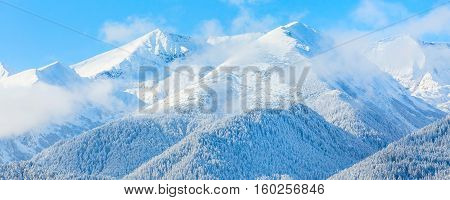 Winter travel vacation nature panoramic background with snow covered mountain peaks and blue sky with clouds closeup