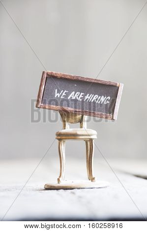 Job recruiting advertisement represented by WE ARE HIRING - tag with an inscription and a golden chair