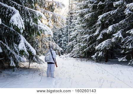 Man on a winter hunt in the woods in winter camouflage