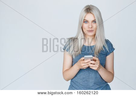 Happy girl in t-shirt texting on a smart phone over grey background with copy space