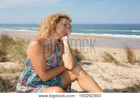 A Pensive Woman On The Waterfront In The Sand