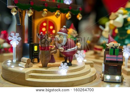 Close-up detail of wooden Christmas toys depicting a scene with Santa Claus a reindeer and his elf. Christmas toys and holidays concept.