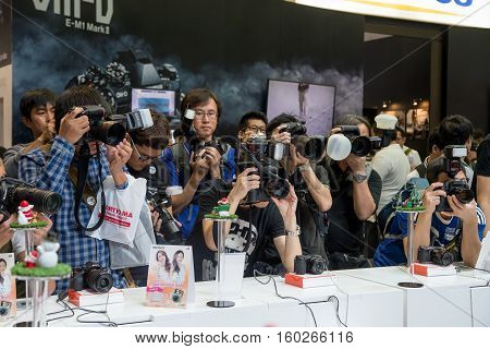 December 2 2016. Multiple photographers with DSLRs and flashes photograph a consumers electronics show in Bangkok Thailand.