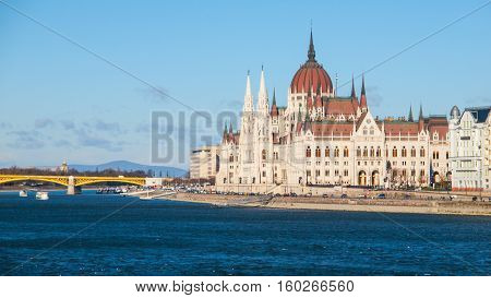 Daytime view of historical building of Hungarian Parliament, aka Orszaghaz, with typical symmetrical architecture and central dome on Danube River embankment in Budapest, Hungary, Europe. It is notable landmark and seat of the National Assembly of Hungary
