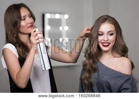 Hairdresser using hairspray on client's hair at salon, Portrait of two beautiful women