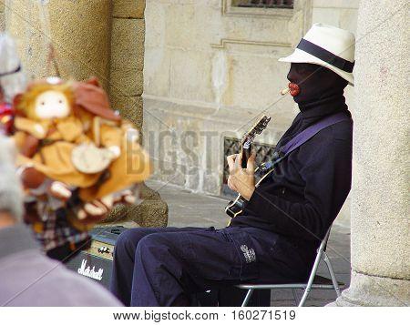 saint yago de compostela street black faced guitar musician