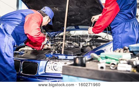 Two mechanics working on a car in a garage
