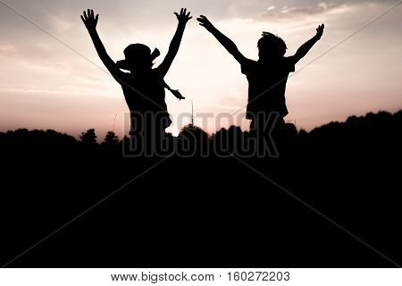 Silhouettes of kids jumping off a cliff at sunset. Little boy and girl jump raising hands up high. Brother and sister having fun in summer. Friendship freedom concept. Fraternal twins on vacation in mountains.