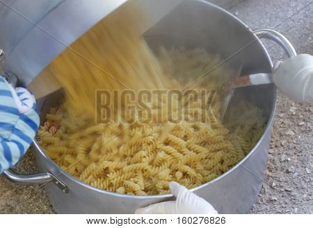 Cook Pours The Pasta Into The Big Pot In The Restaurant