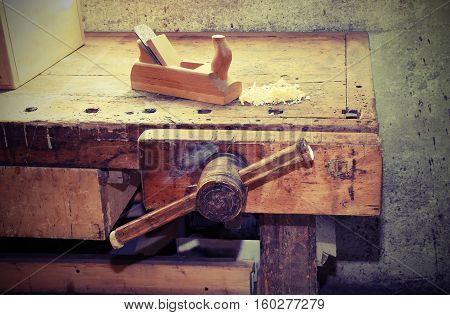old wooden plane on the table of the workshop of carpenter with a wooden vise