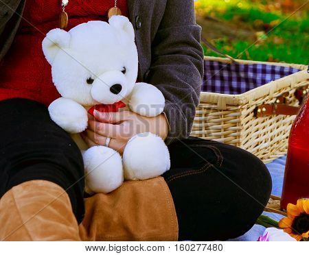 A pregnant mother holds her childs teddy bear.