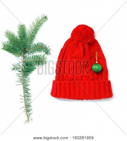 picture of a red winter woolen hat and pine twigs on white. studio shot