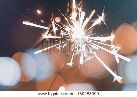 Night background with a sparkler. Sparkler Bokeh Colorful sparkler. Shallow focus