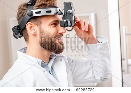 Eye doctor with ophthalmologic binocular device for checking vision with the eye chart on the background in the cabinet