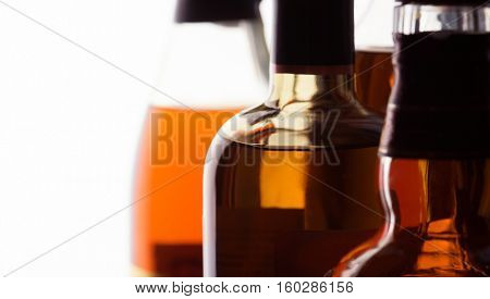 Scotch whisky and bourbon bottles on an counter, close-up. Shallow depth of field.