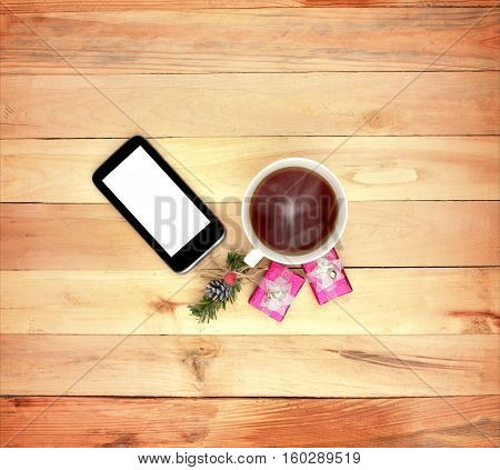 Smartphone gifts. and a cup of hot drink on a wooden background. Top view. Christmas. Morning surprise. Concept. Love. Care. Attention. Home comfort. Modern communication. Technology.