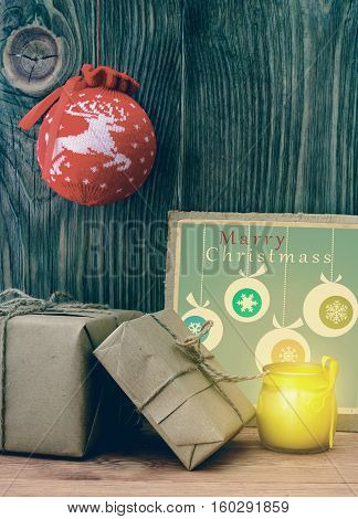 Christmas Composition with gift boxes wrapped in kraft paper, retro greeting card on wooden background.
