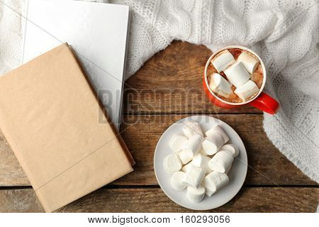 Cup of fresh coffee with marshmallow  and knitted plaid on wooden background, top view