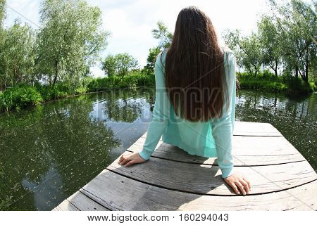 Woman sitting on wooden pier and enjoying beauty of the nature