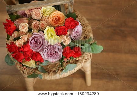 Beautiful flower composition on wicker chair