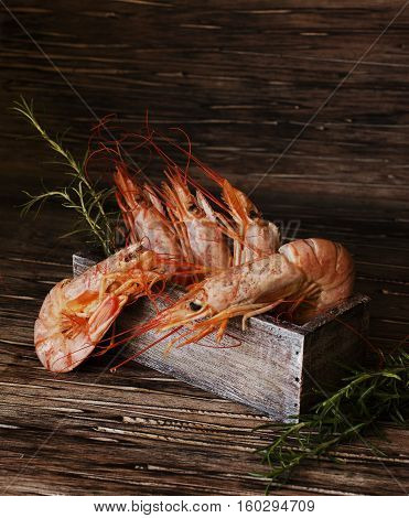 raw or cooked shrimp with rosemary in a wooden box on an old table, selective focus