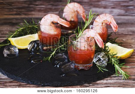 appetizer of shrimp cocktail with rosemary and sauce in cups on a wooden table, selective focus