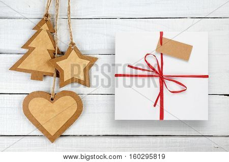 Christmas decorations and gift box with tag on white wooden background