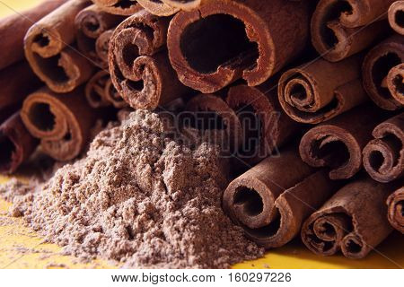 heap of cinnamon sticks close up and cinnamon powder on a yellow background
