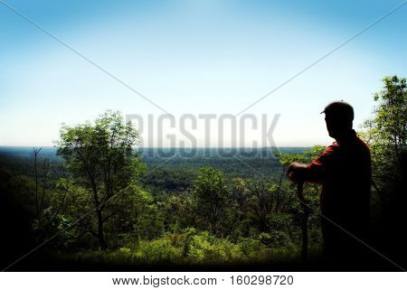 A man climbs to the highest peak and overlooks his achievement with a silent awe.