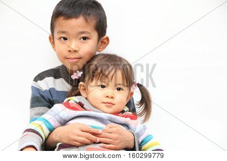 Japanese brother and sister sitting on his knee (7 years old boy and 2 years old girl)