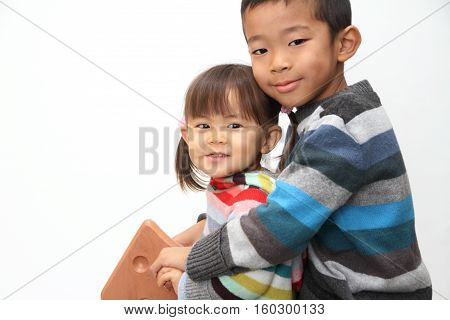 Japanese brother and sister playing with rocking horse (7 years old boy and 2 years old girl)