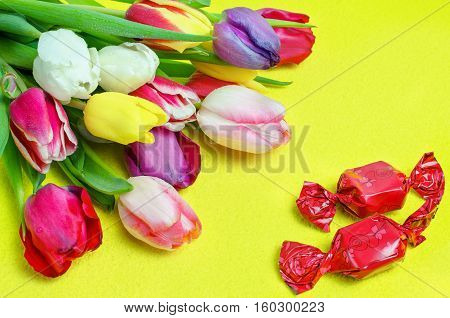 Candies basket and bouquet of tulips on Yellow background. Gift for a holiday. Valentine's Day. International Women's Day.