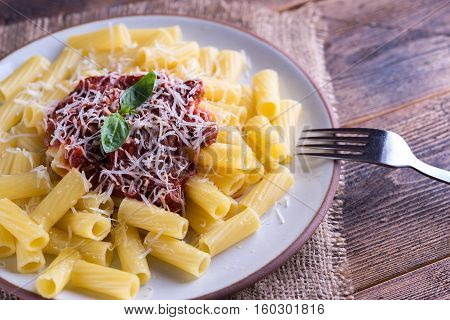 Pasta with tomato sauce and parmigiano on natural wooden table with fork.