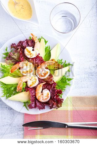 Avocado shrimp salad with mustard sauce with knife and fork.