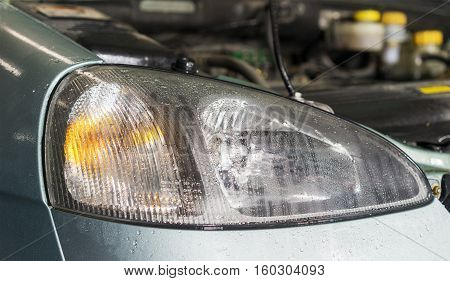 Car headlights close up image with rain drops as background