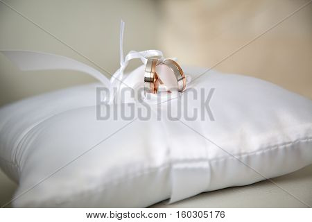 Set of white and red gold wedding rings tied with a decorative ribbon on a white satin cushion.