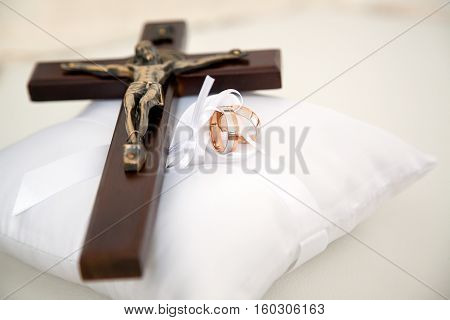 Wedding rings and small wooden Christian cross with Christ placed on white decorative cushion.jpg