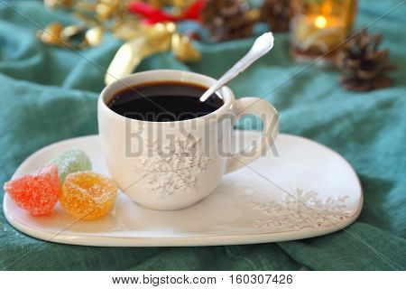 New Year drink: cup of coffee and pine cones burning candle and colorful candy