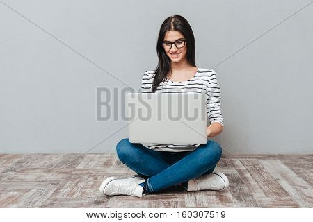 Happy young woman wearing eyeglasses sitting on floor while using laptop. Looking at laptop.