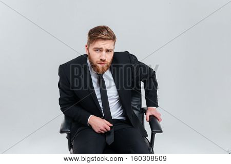 Serious Business man in black suit sitting on armchair, peers at camera and holding one hand to armchair. Isolated gray background