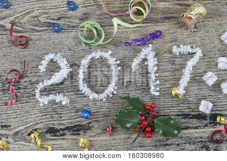 2017 in white tinsel on wooden background with Christmas toys