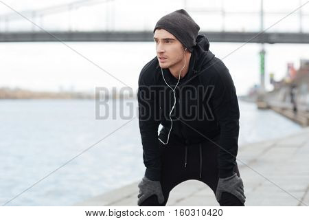 Confident young man athlete resting after running outdoors in autumn