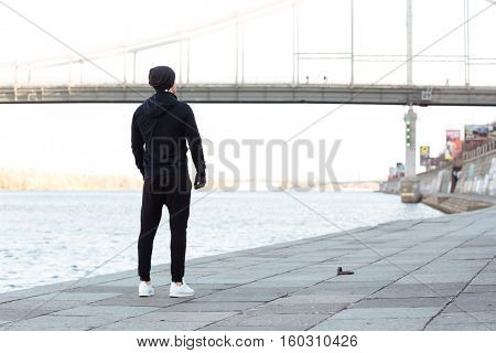 Back view of man athlete standing and resting after running outdoors