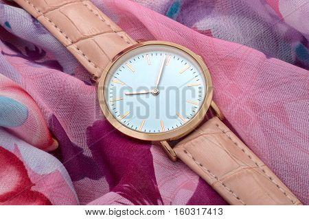 Pink band wrist watch on silk fabric background