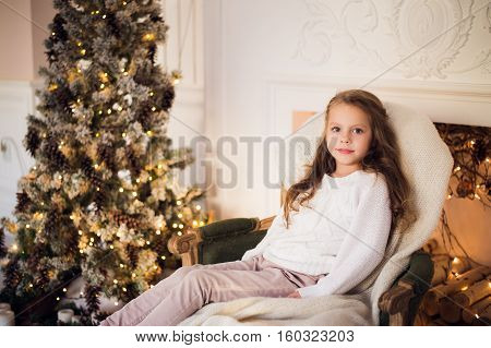 5 years old little girl sitting on cozy wrapped in a blanket chair Christmas tree morning at home.