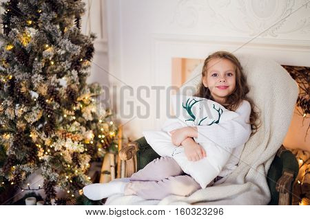 Portrait of a cute little girl embracing cushion at home against christmas tree.
